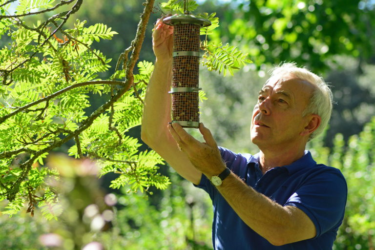 Richard Jackson feeding the birds in his garden with bird food