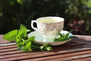 ornate teacup and saucer with mint leaves