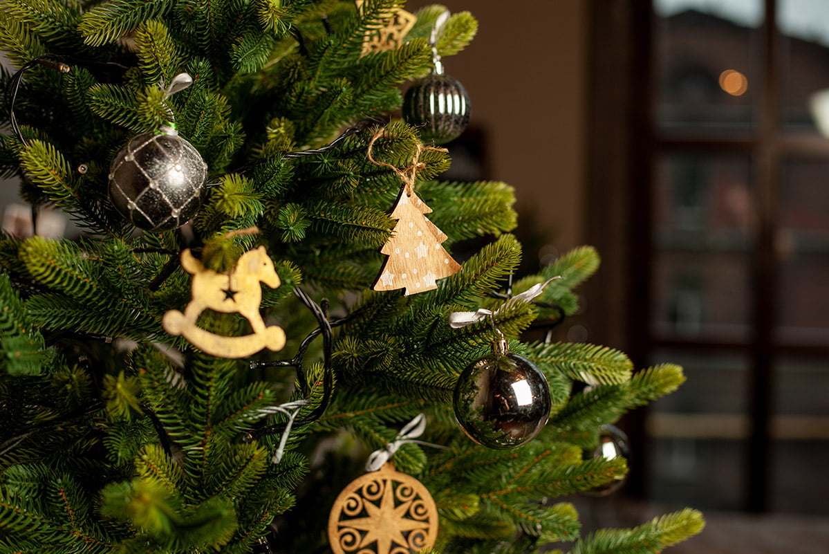 close of decorated Christmas tree with natural, gold and black decorations