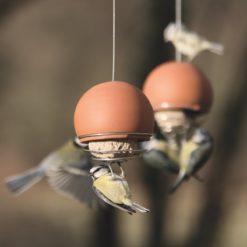 Birdball Belle Bird Feeders in terracotta with blue tits feeding