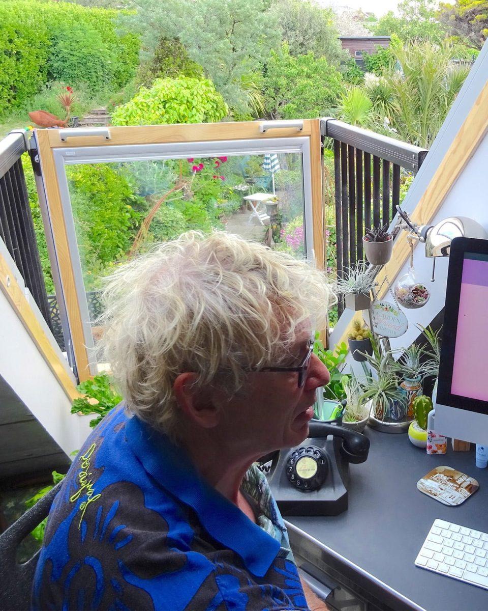 Geoff Stonebanks working at his desk overlooking Driftwood garden