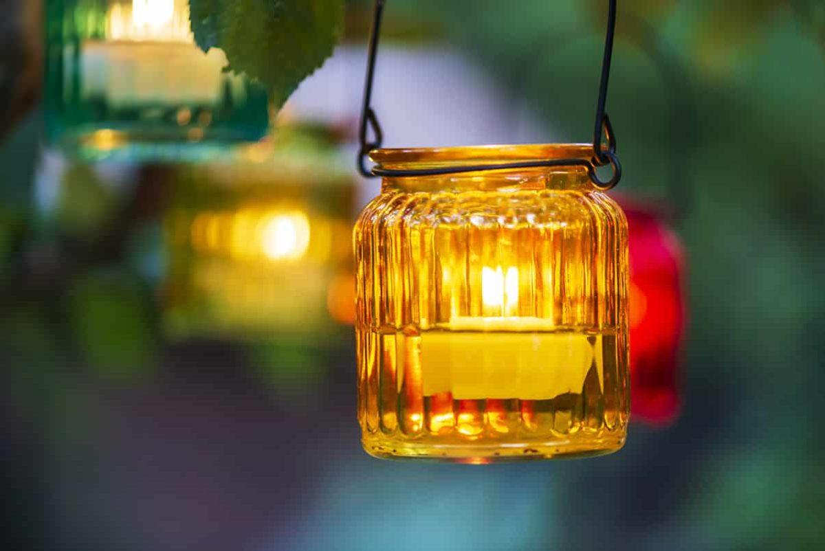 tea light in glass jar hanging from tree